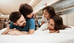 Family checking softness of the orthopedic mattress and lying on the bed in a furniture store